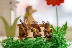Rabbits sitting on a bench near a window. Decoration rabbits sitting on a bench near a window Stock Image