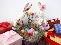 Rabbits look at the basket with colorful eggs for Easter. Rabbits are sitting on the boxes with a bouquet of pussy willow and basket of colorful eggs on Easter Royalty Free Stock Images