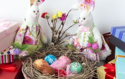 Rabbits look at the basket with colorful eggs for Easter. Rabbits are sitting on the boxes with a bouquet of pussy willow and basket of colorful eggs on Easter Royalty Free Stock Image