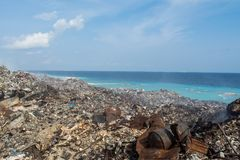 Rabble at the garbage dump near the beach full of smoke, litter, plastic bottles,rubbish and trash at tropical island. Rabble at the garbage dump near the beach Stock Image