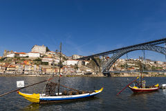 Rabelo Boats `Barcos Rabelos` in the Douro River with the city of Porto and the old D. Luis Bridge `Ponte Dom Luís on the back royalty free stock photography