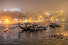 Rabelos and Porto on a night with a sea mist, Portugal. Rabelos, the old river cargo boats as was used by the Port Houses moored on the River Douro. The stock images