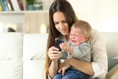 Rabieta del bebé que lucha con su madre para un teléfono elegante fotografía de archivo libre de regalías