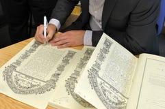 Rabijn die de Joodse Prenuptial Overeenkomst van Ketubah ondertekenen stock foto's
