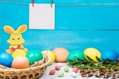 Rabit y huevos de Pascua en una cesta, pintada en diverso color en un fondo azul con un lugar para la inscripción y fotografía de archivo
