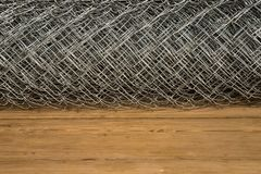 Rabitz grid in a roll on a wooden background stock images