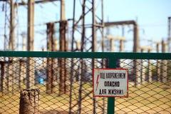 Rabitzomheining rond industriezone met waarschuwingsbord 'onder voltage, gevaar voor uw leven! ' royalty-vrije stock afbeelding