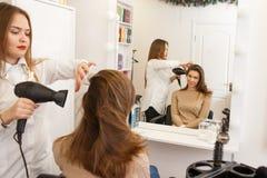 Raboteuse de cheveux faisant le style pour un client féminin Photos libres de droits