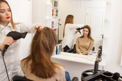 Raboteuse de cheveux faisant le style pour un client féminin Photographie stock