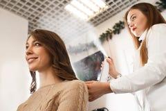 Raboteuse de cheveux pulvérisant avec le vernis à la coiffure du ` s de client Images stock