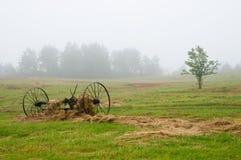 Raccattafieno nel campo in nebbia Fotografia Stock