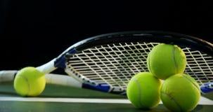 Racchetta del primo piano sistemata sulle palline da tennis 4k video d archivio