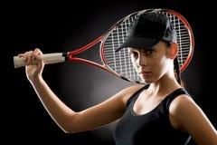Racchetta della tenuta di sport della donna di tennis sul nero Fotografia Stock