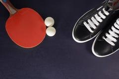 Racchetta di ping-pong, palle e scarpe da tennis nere con i pizzi bianchi su un fondo scuro Immagine Stock