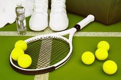 Racchetta di tennis con le palle e le scarpe da tennis, bottiglia di acqua, borsa della palestra, a Immagini Stock