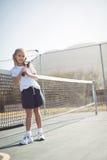 Racchetta di tennis della tenuta della ragazza mentre sedendosi dalla rete Immagine Stock Libera da Diritti