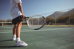 Racchetta di tennis della tenuta della ragazza mentre stando sulla corte Fotografia Stock Libera da Diritti