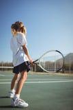 Racchetta di tennis della tenuta della ragazza sulla corte Immagini Stock Libere da Diritti