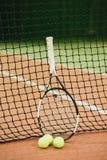 Racchetta di tennis e 3 palle sul primo piano di griglia del campo da tennis Strumentazione di sport immagine stock libera da diritti