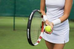Racchetta e palla della tenuta del tennis in mani Immagini Stock Libere da Diritti