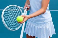 Racchetta e palla di tennis della tenuta del tennis a disposizione sul campo da tennis Immagini Stock