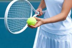 Racchetta e palla di tennis della tenuta del tennis a disposizione sul campo da tennis Immagini Stock Libere da Diritti