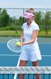 Racchetta e palla di tennis della tenuta del tennis sul campo da tennis Fotografie Stock