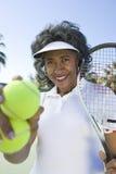 Racchetta e palle femminili della tenuta del tennis Immagini Stock