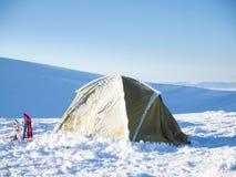 Racchette da neve e tenda contro il cielo blu Fotografie Stock Libere da Diritti