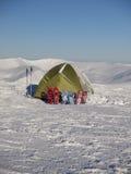 Racchette da neve e tenda su neve nelle montagne Immagini Stock