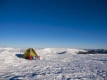 Racchette da neve e tenda su neve nelle montagne Fotografie Stock Libere da Diritti