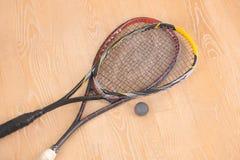Racchette e palla di equiment di sport sul pavimento immagine stock