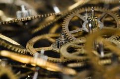 Raccolta degli ingranaggi metallici d'annata dell'orologio su una superficie nera Immagini Stock
