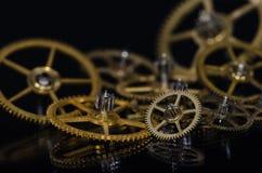 Raccolta degli ingranaggi metallici d'annata dell'orologio su una superficie nera Immagine Stock