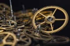 Raccolta degli ingranaggi metallici d'annata dell'orologio su una superficie nera Fotografie Stock