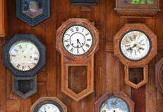 Raccolta degli orologi di legno d'annata sul fondo di legno della parete fotografia stock