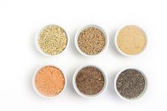 Raccolta dei chicchi differenti su fondo bianco Vista superiore di grano saraceno, chia, lino, amaranto, lenticchie, cuscus fotografia stock libera da diritti