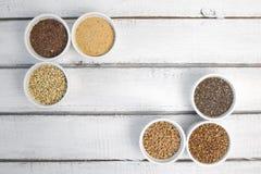 Raccolta dei chicchi differenti su fondo grigio Vista superiore di grano saraceno, chia, lino, amaranto, lenticchie, cuscus, gran fotografia stock