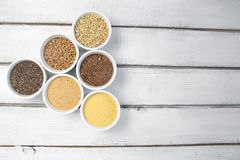 Raccolta dei chicchi differenti su fondo grigio Vista superiore di grano saraceno, chia, lino, amaranto, lenticchie, cuscus, gran immagine stock