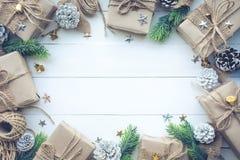 Raccolta dei contenitori di regalo avvolta in carta kraft con il pino del confine su legno bianco Fotografia Stock