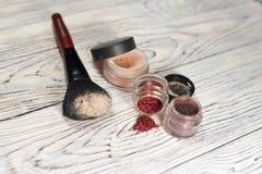 Raccolta dei cosmetici per il truccatore Powder, i pigmenti, lo scintillio, le spazzole e l'eye-liner foto dello studio su un fon Fotografia Stock Libera da Diritti