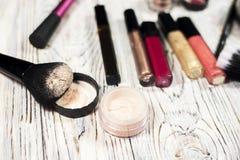 Raccolta dei cosmetici per il truccatore Powder, i pigmenti, lo scintillio, le spazzole e l'eye-liner foto dello studio su un fon Fotografia Stock