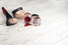 Raccolta dei cosmetici per il truccatore Powder, i pigmenti, lo scintillio, le spazzole e l'eye-liner foto dello studio su un fon Fotografie Stock