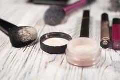 Raccolta dei cosmetici per il truccatore Powder, i pigmenti, lo scintillio, le spazzole e l'eye-liner foto dello studio su un fon Fotografie Stock Libere da Diritti
