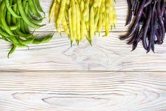 Raccolta dei fagioli a cespuglio verdi, gialli e porpora, piselli aperti su fondo di legno fotografia stock libera da diritti