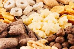 Raccolta dei fiocchi di mais sul primo piano dei cereali diversi, fondo decorativo Immagini Stock