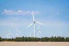 Raccolta dei generatori eolici bianchi contro un cielo blu Fotografia Stock