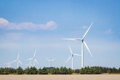Raccolta dei generatori eolici bianchi contro un cielo blu Fotografie Stock