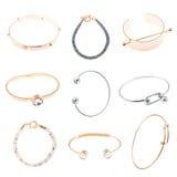 Raccolta dei gioielli dei braccialetti dell'argento e dell'oro isolati su briciolo Fotografia Stock
