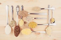 Raccolta dei grani di cereali in cucchiai d'argento su fondo di legno bianco Immagine Stock